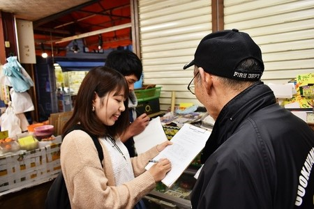 商店街でアンケート調査をする学生